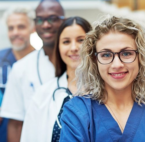 Multiethnic doctor team standing in a hospital and looking at camera.